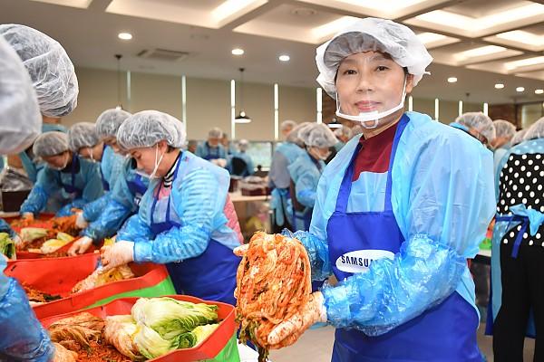 절인배추에 김장재료를 넣어 김장김치를 만들고 있는 봉사자들 사진